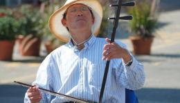 man playing Chinese instrument